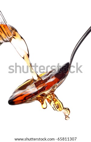 Malt vinegar being poured from a bottle, isolated on white