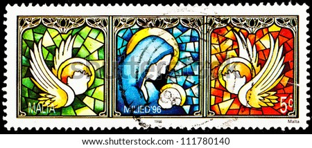 MALTA - CIRCA 1996:  A stamp printed in Malta shows the Virgin Mary holding the baby Jesus with doves with Jesus' head on them, circa 1996. - stock photo