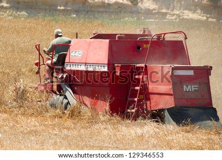 MALTA, GOZO - JUNE 7: A farmer at Gozo Island harvests a field being almost too small to turn-over the harvester.  June 7th, 2012 at Gozo, Malta.