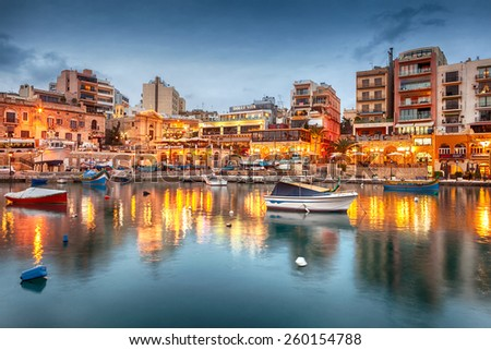 MALTA - JANUARY 19 2015: Spinola Bay with boats in front of famous touristic restaurants at St Julian, Malta - stock photo