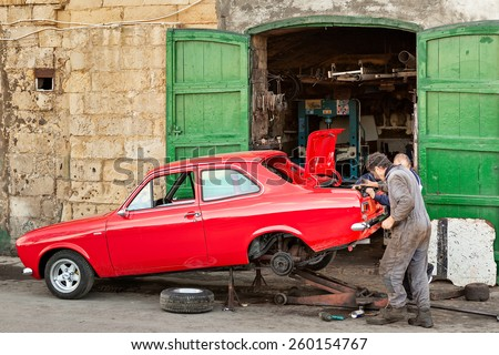 MALTA - JANUARY 21 2015: Two mechanics restoring old vintage red car near their garage at Valetta, Malta