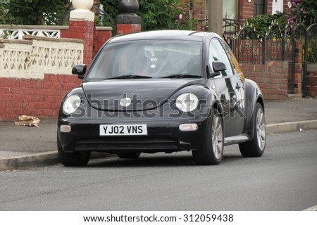MALTBY, SOUTH YORKSHIRE, UK - CIRCA AUGUST 2015: black Volkswagen New Beetle car in a street of the city centre. - stock photo