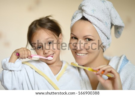 Mama and her little daughter brushing their teeth - stock photo