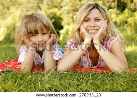 Mama and her little daughter lie on the grass - stock photo