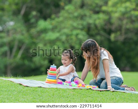 Mama and her little daughter play toy on the grass - stock photo