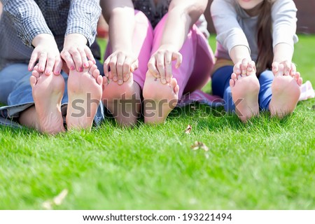 Mama and her little daughters playing on grass - stock photo