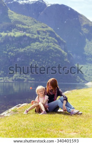 Mama with daughter sitting on the shore fjord, Norway