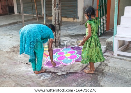 Mamallapuram, Tamil Nadu, INDIA - January 25: Indian mother and daughter painting mandala in front of their home on the street in Mamallapuram on January 25, 2013. - stock photo