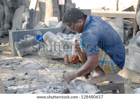 MAMMALAPURAM, INDIA - JAN 25:An artisan, inhaling unhealthy stone dust causing serious lung disease pneumoconiosis while making statues of Gods and Goddesses on January 25, 2013 in Mammalapuram, India