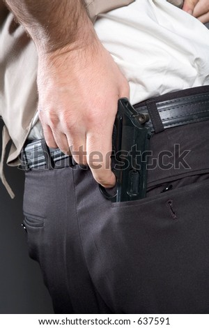 Man a getting pistol from a back pocket of trousers - stock photo