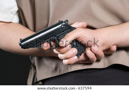 Man a holding pistol behind a back - stock photo