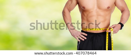 Man abdomen with measuring tape over blue background. - stock photo
