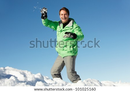 Man About To Throw Snowball Wearing Warm Clothes On Ski Holiday In Mountains - stock photo