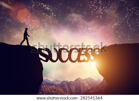 Man about to walk over precipice on SUCCESS word bridge. Dream sky and mountains. Motivation, ambition, business concept. - stock photo