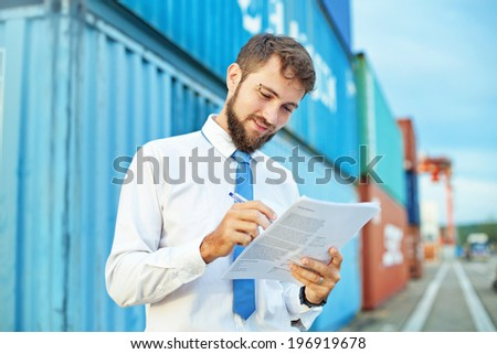 Man accepting goods at a port checking them in his list - stock photo