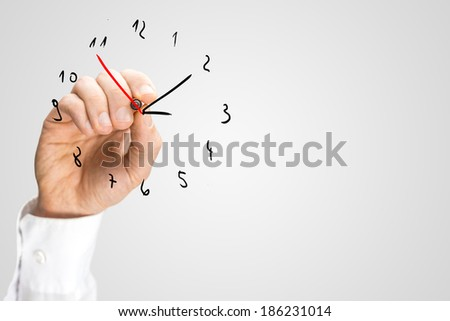 Man adding a second hand to a hand-drawn clock on a virtual interface with a red marker pen in a concept of deadlines, time management, and punctuality. - stock photo