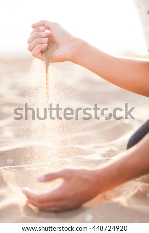 Man adding coarse sand to a heap with his hands. Very shallow depth-of-field and motion blur.