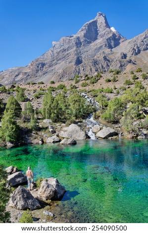 Man admires majestic blue mountain lake in Tajikistan - stock photo
