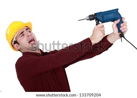 Man afraid of a power drill - stock photo