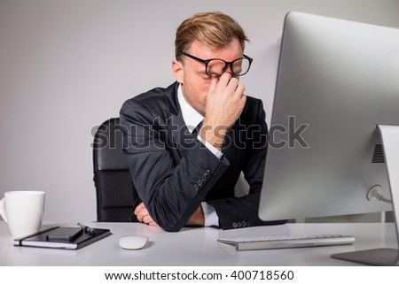 Man after long day holding his glasses  - stock photo