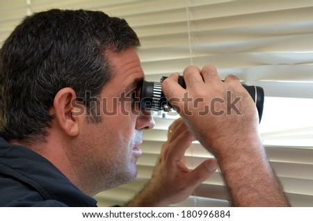Man (age 35-40 ) looks and searches with binoculars and  looks out through Venetian blinds. Concept photo of curious, spy, nosy man. - stock photo
