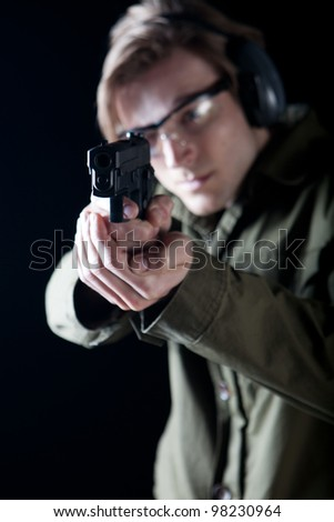 Man aiming a gun with protective gear - stock photo