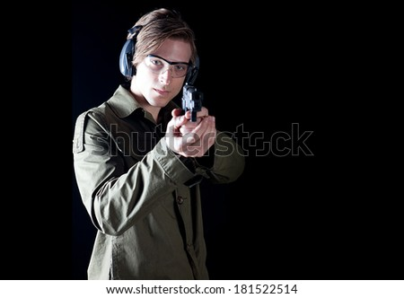 Man aiming a hand gun wearing protective gear - stock photo