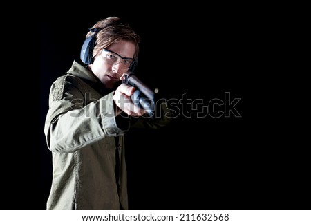 Man aiming a shotgun wearing protective gear - stock photo