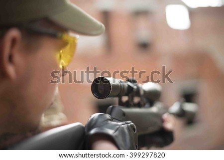 Man aiming at a target and shooting an automatic rifle for strikeball. Focus on the rifle sights. - stock photo