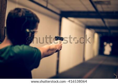 Man aiming pistol at target in indoor firing range or shooting range - stock photo