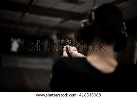 Man aiming revolver pistol at target in indoor firing range or shooting range - stock photo
