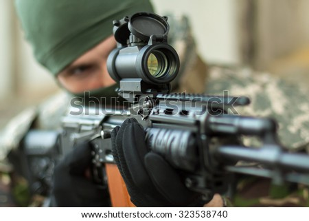 man aiming with an AK-47 with reflex sight - stock photo