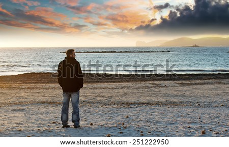 man alone at the beach in winter under a colorful sky at dusk - stock photo