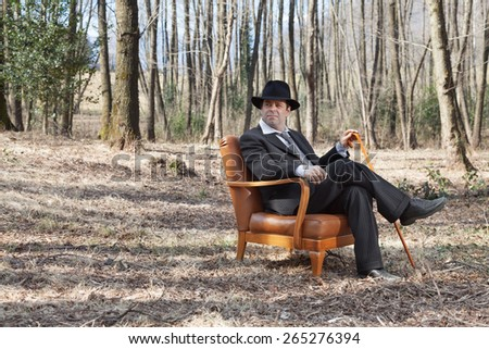 man alone in the woods sitting on a armchair