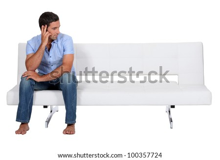 Man alone on the couch - stock photo