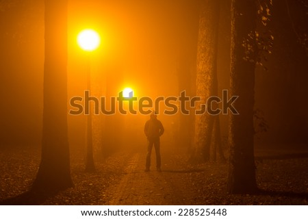 Man alone standing in the middle of a lane on a foggy night. - stock photo