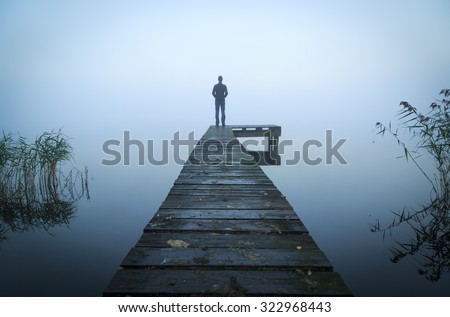 Man alone standing on the end of a jetty during a foggy, gray morning.