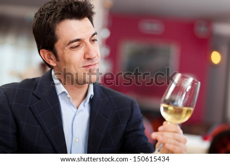 Man analyzing a white wine - stock photo