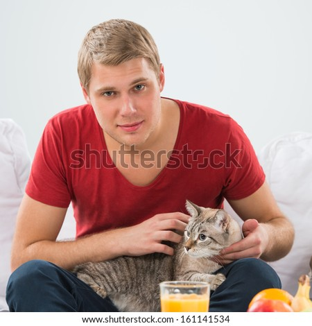 Man and a cat at home. Handsome man cuddling his tabby cat on sofa - stock photo