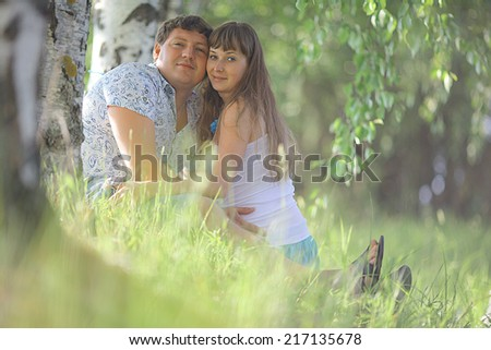 man and a pregnant woman happy nature