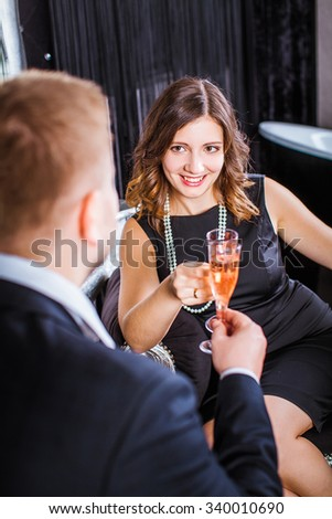 man and a woman drink champagne in a black bedroom - stock photo