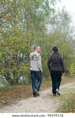 Man and a woman having a walk in the forest.