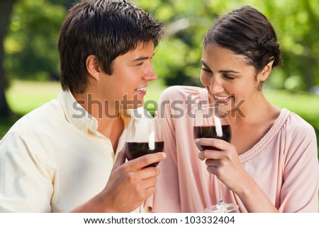 Man and a woman holding glasses of red wine while smiling in a park with trees in the background