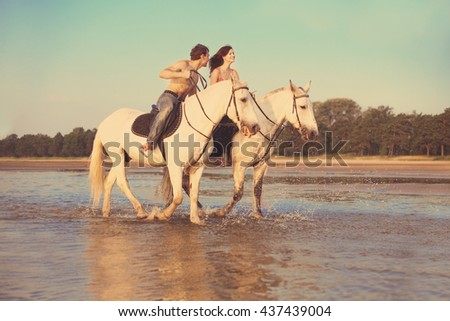 Man and a woman in love with the sea on horseback - stock photo