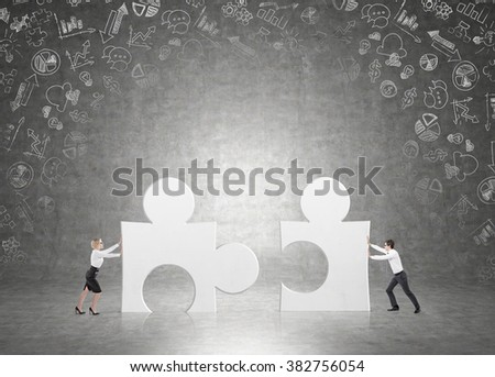 man and a woman pushing matching puzzles to each other. Black background with small business icons. Concept of cooperation.