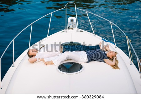 Man and a woman relaxing on a yacht on summer day. They are a lovley cople of people over 50. - stock photo