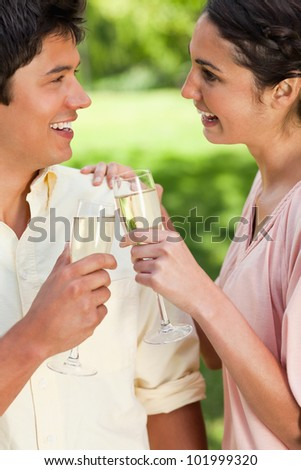 Man and a woman smiling while looking at each other as they touch glasses of champagne in a park