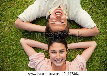 Man and a woman smiling while lying head to head with both of their arms resting behind their neck on the grass