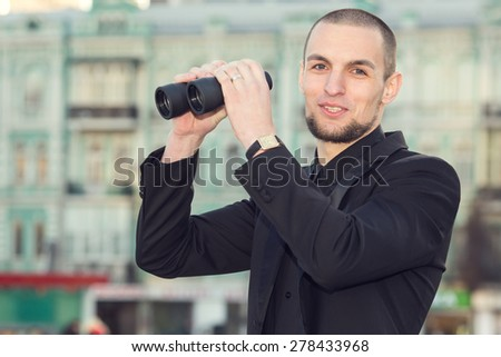 Man and binoculars. Business man with binoculars in his hand against the background of the streets downtown. Security man holding binoculars. Looking for a job. Man with spying. Service monitoring. - stock photo