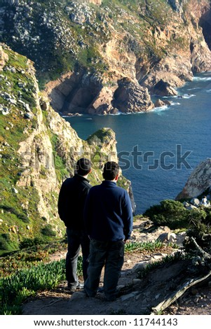 man and boy contemplating the sea - coastline of Portugal
